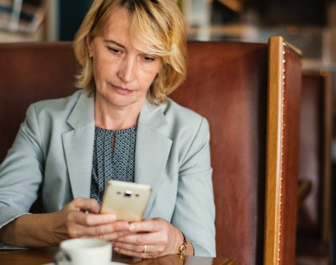 woman sitting at booth with coffee looking at her phone