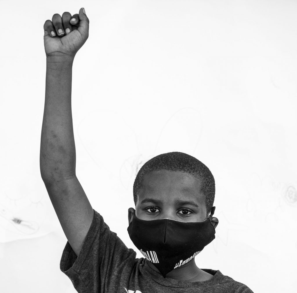 young boy holding fist in the air for the black lives movement